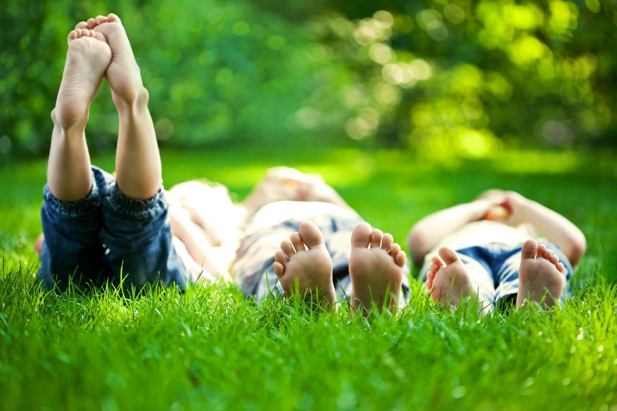 Group of happy children lying in the grass in the spring